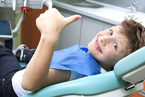 Smiling young boy in dental chair giving thumbs up
