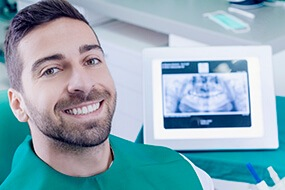 man smiling in front of cavity machine