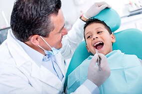 dentist cleaning young boys smile