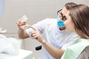 Dentist showing patient an implant supported fixed bridge model