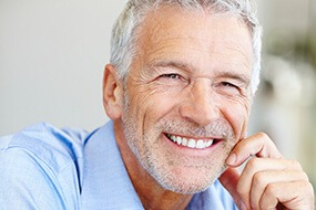 man smiling in blue shirt off into the distance