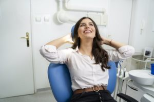 Relaxed woman smiles while visiting her Hutchinson sedation dentist