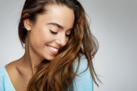 Woman with brown hair smiling after seeing a cosmetic dentist