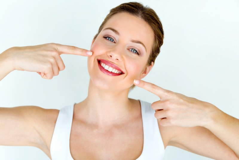 young attractive woman smiling after receiving treatment from cosmetic dentist